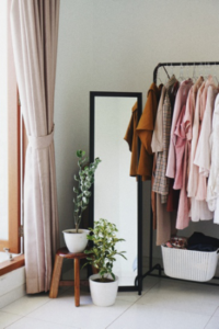 Clothing rack with various garments, next to a mirror and plants