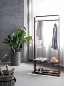 Clothing rack with a plant and basket in a decluttered home.